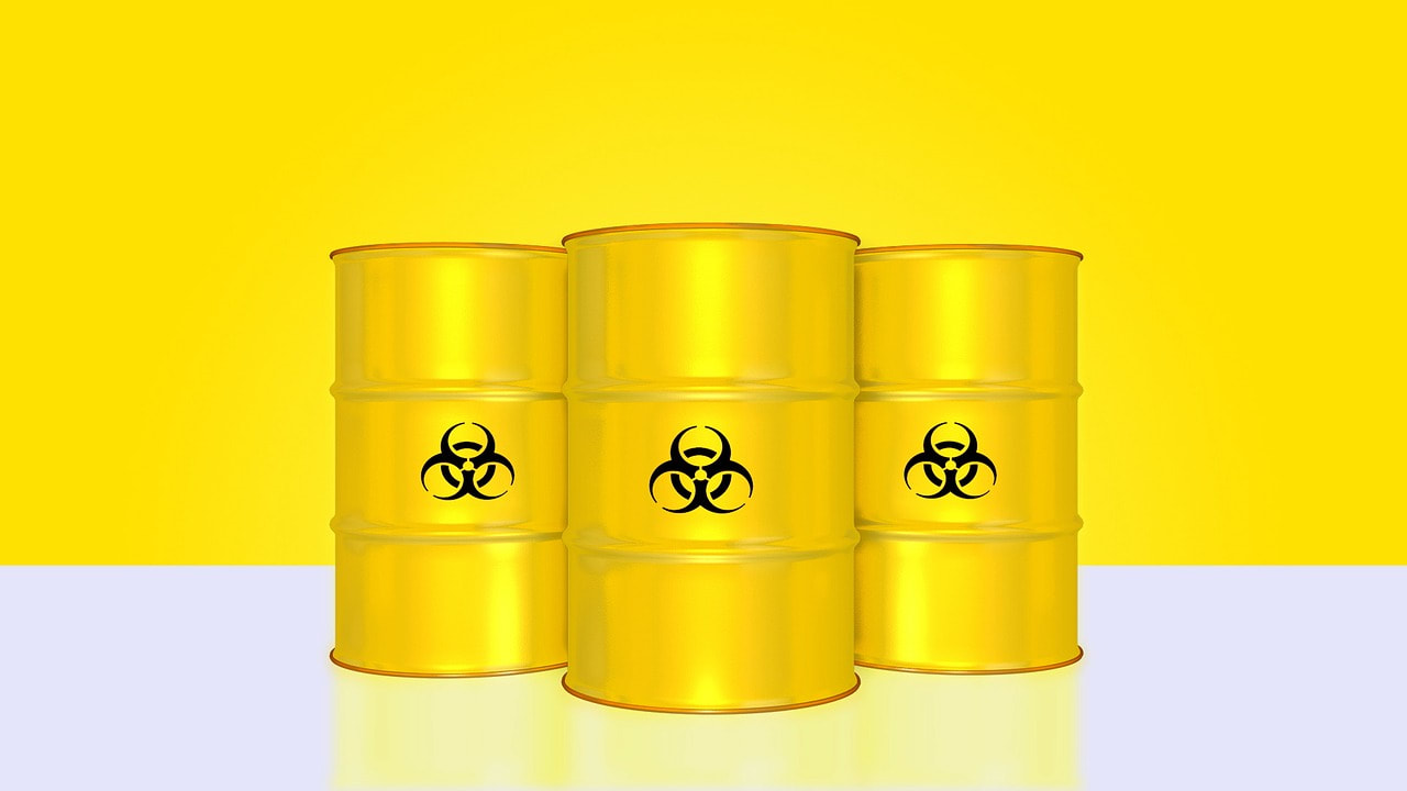 yellow background, white floor. in the centre are 3 barrels, also in bright yellow, with toxic looking signs painted on the middle of each barrel.