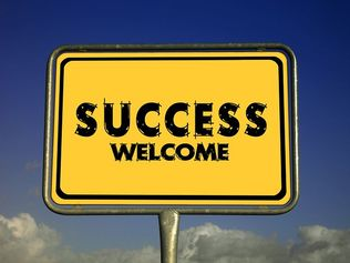 Large yellow sign with the words success welcome written in black.
