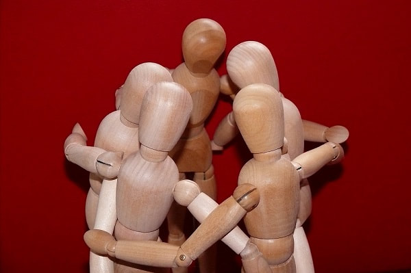 Models of little stick men all huddled in a circle with their heads together