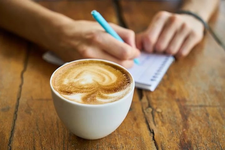 person writing on notepad with a cup of coffee