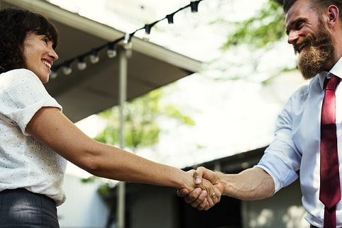 Image af a man and women dressed in work clothes smiling and shaking hands