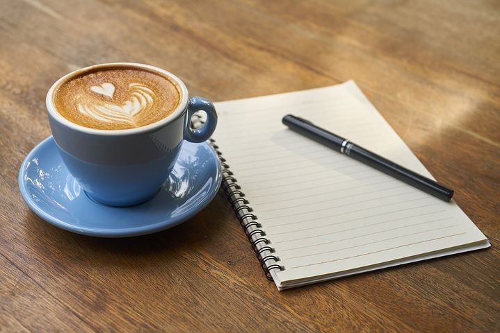 Photo of a blue coffee cup and note paper and pen on a wooden table