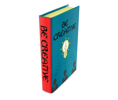 A book that is standing on its end and the front cover is blue with a yellow bulb in the middle and above it reads be creative