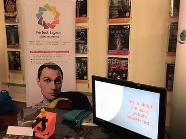 The Perfect Layout stand at the HCCI showcase event at the Queens Theatre, Hornchurch. Photo shows the Perfect Layout banner and table with television and prosecco and chocolates.
