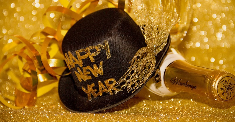 A festive scene of gold with a black hat and gold bottle of drink. on the hat is written happy new year.