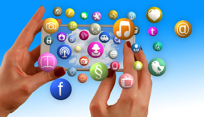 Photo of two hands holding a mobile phone with app icons floating around the image
