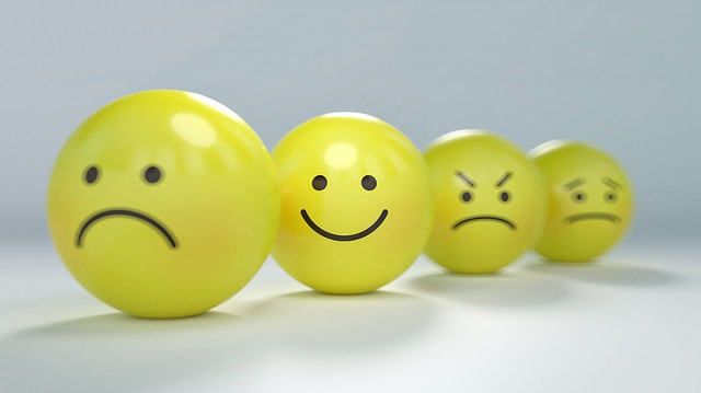 Picture of yellow balls with face expressions drawn on them. Happy face is in focus.